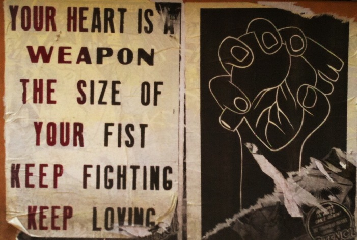 "wheatpasted street art. on the left, text in all caps stating ""your heart is a weapon the size of your fist keep loving keep fighting"". on the right a white drawing of a hand holding a heart on a black background."