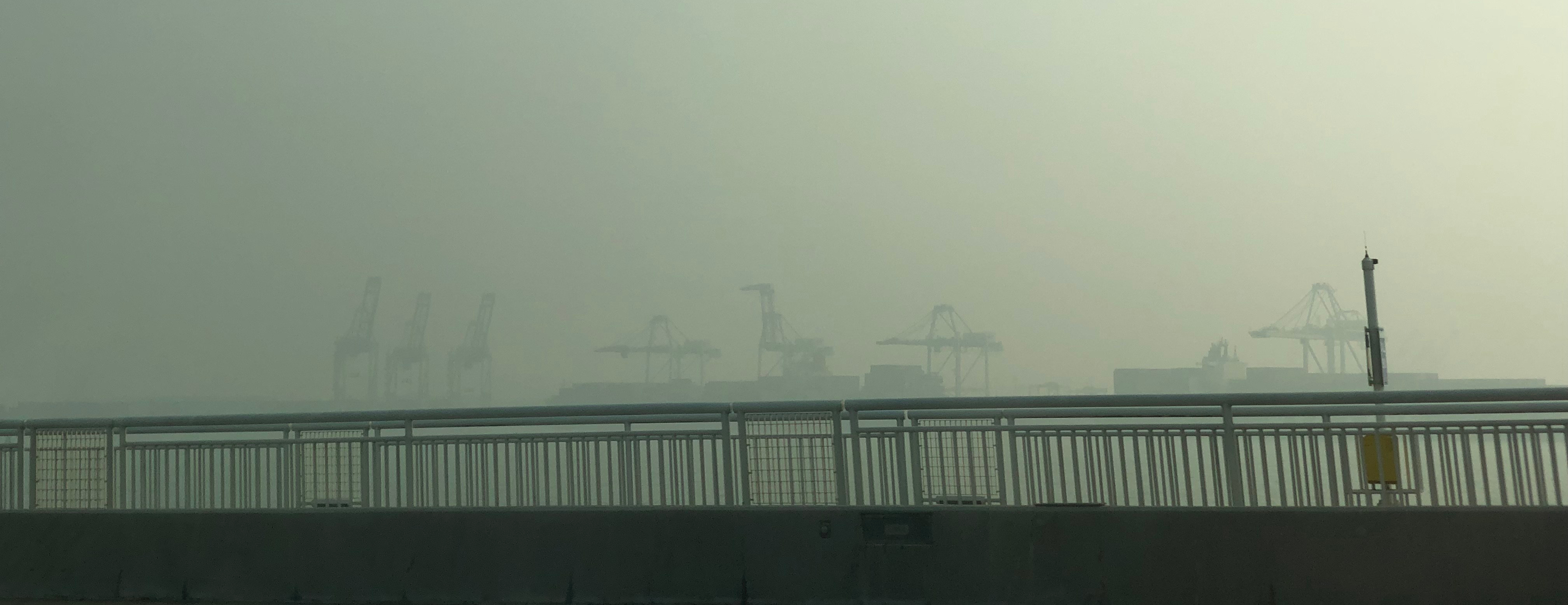 shipping container cranes are hidden by smoke in the distance beyond the bridge's railing